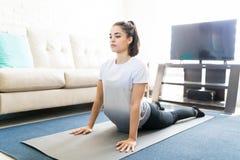 Yoga di pratica di posa della cobra della donna Fotografie Stock Libere da Diritti