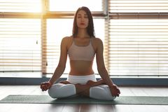 Yoga di pratiche della giovane donna alla palestra dalla finestra fotografia stock