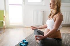 Yoga di rilassamento e di pratica della donna incinta a casa Immagine Stock