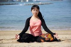 Yoga di seduta della donna giapponese su una spiaggia Fotografia Stock