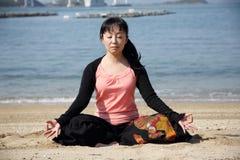 Yoga di seduta della donna giapponese su una spiaggia Fotografie Stock