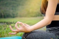Yoga di seduta della giovane donna vicino al fiume Concetto del lifestyl sano Fotografie Stock