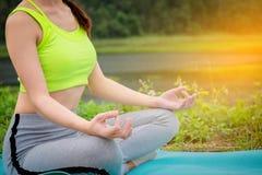 Yoga di seduta della giovane donna vicino al fiume Concetto del lifestyl sano Fotografia Stock