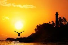 Yoga dichtbij vuurtoren Stock Afbeeldingen