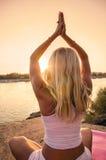 Yoga door de rivier bij zonsondergang stock foto