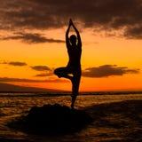 Yoga durch den Ozean Stockfotos
