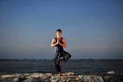 Yoga durch den Strand Stockfoto