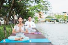 Yoga e meditazione di pratica della donna sulla stuoia vicino alla laguna con il ragazzo immagini stock