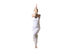 Yoga Eagle Pose. Beautiful fitness model practices yoga or pilates, standing in yoga Eagle Pose, Garudasana, front view, studio shot, isolated Royalty Free Stock Photos