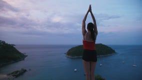 Yoga-Eignungsübung der Frau übende auf hohem Platz mit überraschender Ansicht von Insel bei Sonnenaufgang stock video