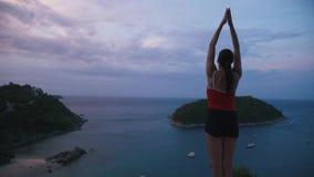 Yoga-Eignungsübung der Frau übende auf hohem Platz mit überraschender Ansicht von Insel bei Sonnenaufgang stock footage