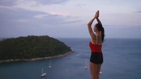 Yoga-Eignungsübung der Frau übende auf hohem Platz mit überraschender Ansicht von Insel bei Sonnenaufgang stock video footage