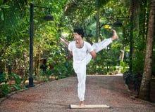 Yoga eine balancierende Haltung des Fahrwerkbeines Stockbild