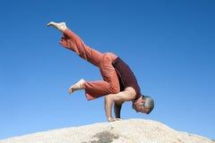 Yoga Eka Pada Bakasana. Man in the yoga pose Eka Pada Bakasana outdoors balanced on a stone surface Stock Photo