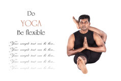 Yoga eka pada shirshasana pose. Yoga eka pada shirshasana foot behind the head pose by Indian man in black cloth isolated at white background. Free space for Stock Photo