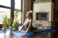 Yoga en casa: Actitud de la cobra imagen de archivo