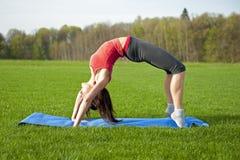 Yoga en el parque. Arqueamiento ascendente Imagen de archivo libre de regalías