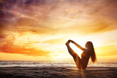 Yoga en la playa de la puesta del sol imagenes de archivo