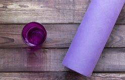 Yoga, estera de la aptitud con el vidrio de agua en piso de madera Fotografía de archivo