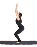 Yoga excercising. Full-length portrait of beautiful woman working out yoga excercise utkatasana on fitness mat Stock Photography