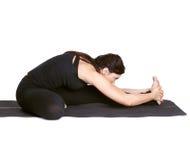 Yoga excercising Janu shirshasana. Full-length portrait of beautiful woman working out yoga excercises Janu shirshasana on fitness mat Stock Photos