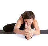 Yoga excercising Janu shirshasana. Full-length portrait of beautiful woman working out yoga exercises Janu shirshasana pose on fitness mat Royalty Free Stock Images