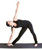 Yoga excercising utthita trikonasana. Full-length portrait of beautiful woman working out yoga excercise utthita trikonasana  on fitness mat Stock Photography