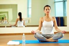 Yoga exercise. Portrait of serene girl doing yoga exercise in gym Royalty Free Stock Photos
