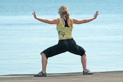 Yoga exercise. A woman on a beach doing yoga exercise Royalty Free Stock Photography