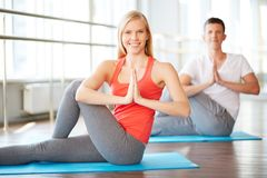Yoga exercise. Portrait of young women doing yoga exercise with guy on background Royalty Free Stock Photo