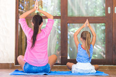 Yoga exercise on terrace by happy mom and girl in lotus position outdoors Stock Images