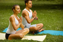 Yoga Exercise. Young couple meditating in Summer Park Royalty Free Stock Photography