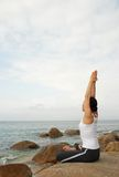 Yoga Exerciser. Young Woman Exercising Yoga in the rocky beach Royalty Free Stock Photo