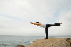 Yoga Exerciser. Young Woman Exercising Yoga balance in the rocky beach Royalty Free Stock Photo