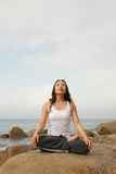Yoga Exerciser. Young Woman Exercising Yoga meditation in the rocky beach Royalty Free Stock Photography