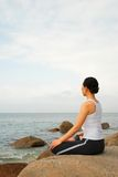 Yoga Exerciser. Young Woman Exercising Yoga meditation in the rocky beach Royalty Free Stock Images