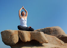 Yoga Exerciser. Young woman exercising yoga meditation over blue sky Royalty Free Stock Image