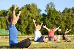 Yoga exercises class breathing technique group of people at the city stadium Russia, Kursk region, Zheleznogorsk, June 2018 stock photo