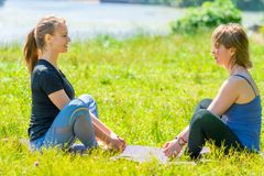Yoga exercises with an individual trainer, young and mature women. In the park royalty free stock photo