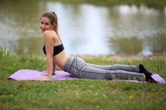 Yoga exercises outdoors. / A young girl / Portrait Royalty Free Stock Photos