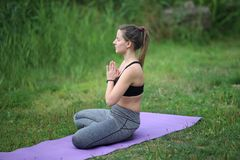 Yoga exercises outdoors. / A young girl / Portrait Royalty Free Stock Photo
