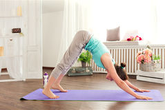 Yoga exercises. Young caucasian woman staying in a pose on the mat downward dog Stock Photography