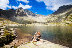 Yoga exercising in Tatry mountains. Exercise yoga everywhere - in slovakian Tatry mountains. Beautiful panorama - Chata Teryho, kotlina Piatich Spisskych plies Stock Photo