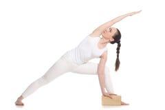Yoga extendida de la actitud del ángulo lateral con el bloque Foto de archivo libre de regalías
