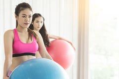 Yoga för asiatiskt folk för grupp praktiserande med yogabollen royaltyfri foto