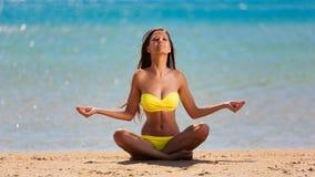 Yoga för baddräkt för brunettkvinnaguling royaltyfria bilder