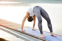 Yoga för bro för yogaflickadanande poserar att vända mot soluppgången på riven Arkivbild