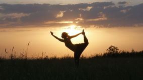 Yoga för dansare för kontur för ung kvinna poserar skrivande in framme av den härliga solnedgången, den Fruska goraen, Novi Sad,
