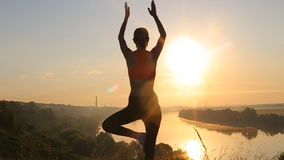 Yoga för kontur för ung kvinna praktiserande på solnedgången stock video