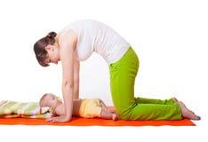 Yoga för moder för ung kvinna behandla som ett barn praktiserande med Arkivfoto